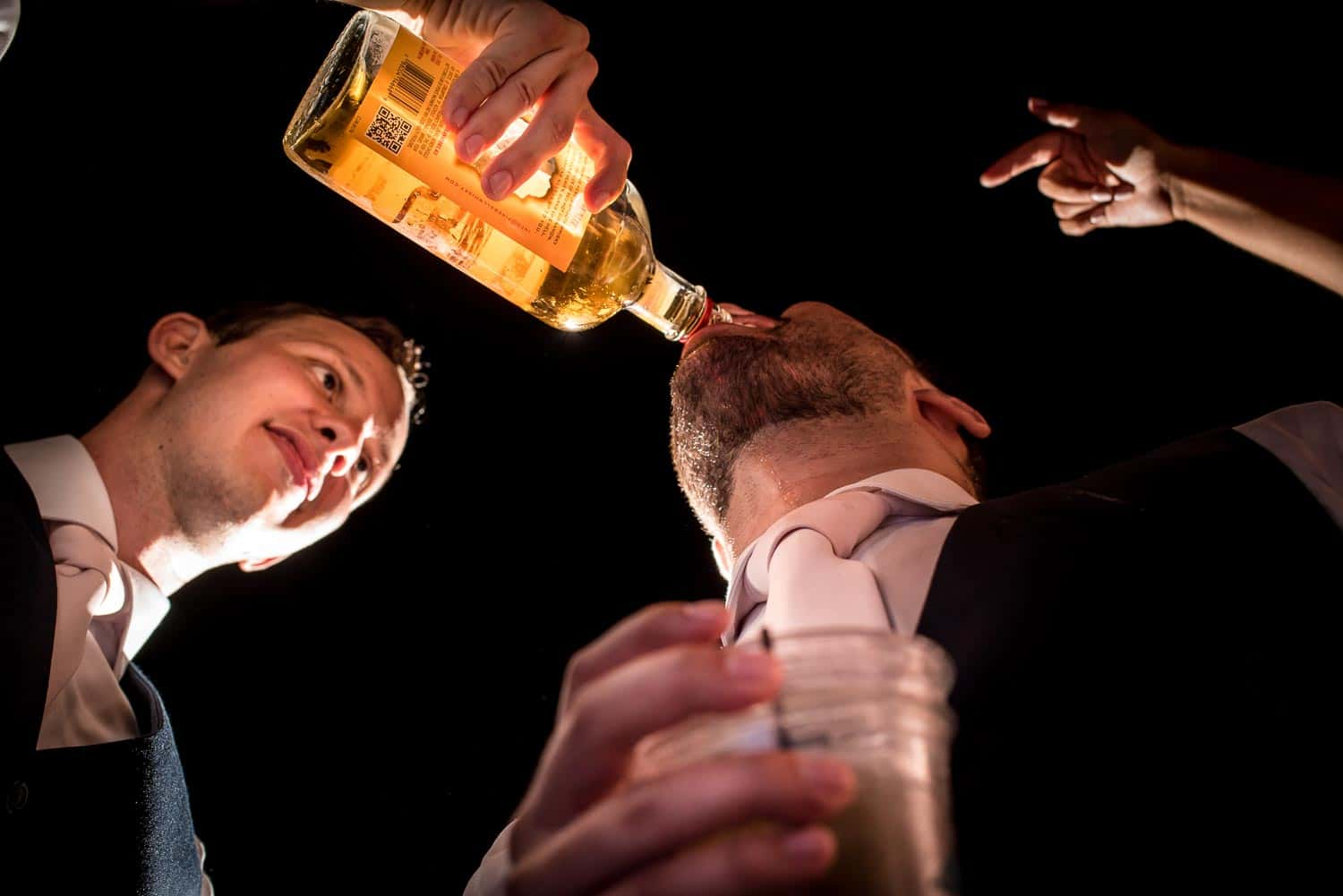 Groomsmen pouring shots into each others mouths