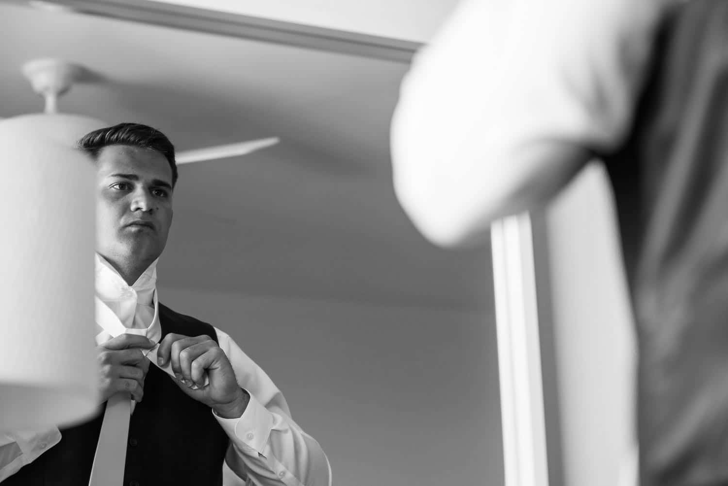 Groom fixing his tie before the wedding BW