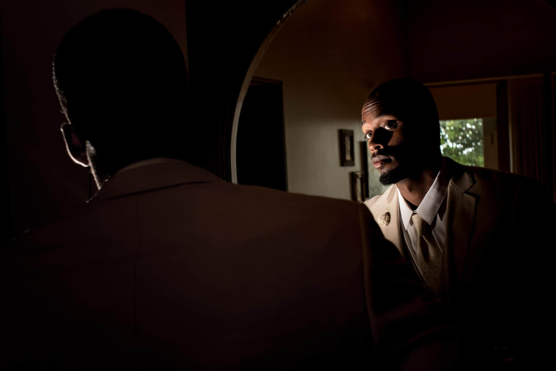 Groom before wedding ceremony looking in mirror