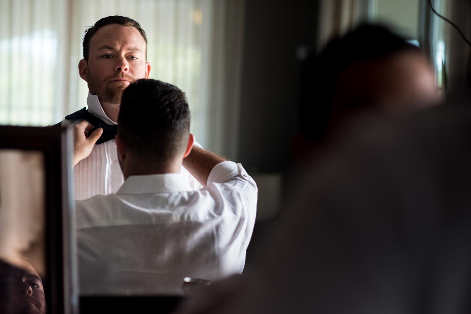 Grooms best man helps the groom tie his bowtie in a mirror before the wedding ceremony.