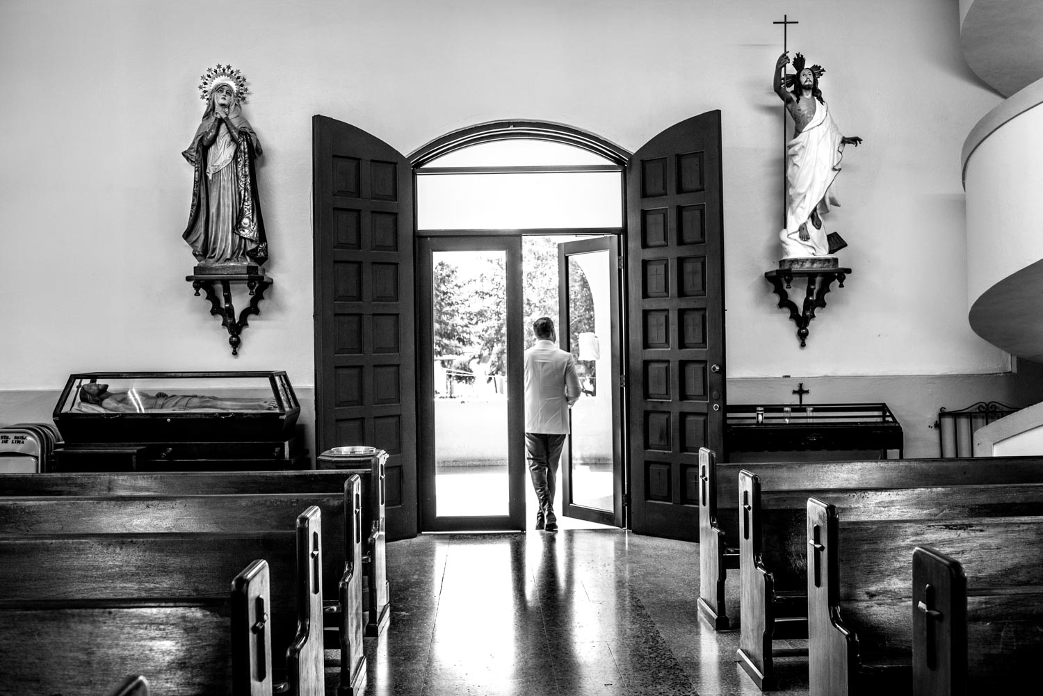 Black and white photograph of the groom going out the church doors. The two icons of the virgin mary and jesus christ are on either side of the doors.
