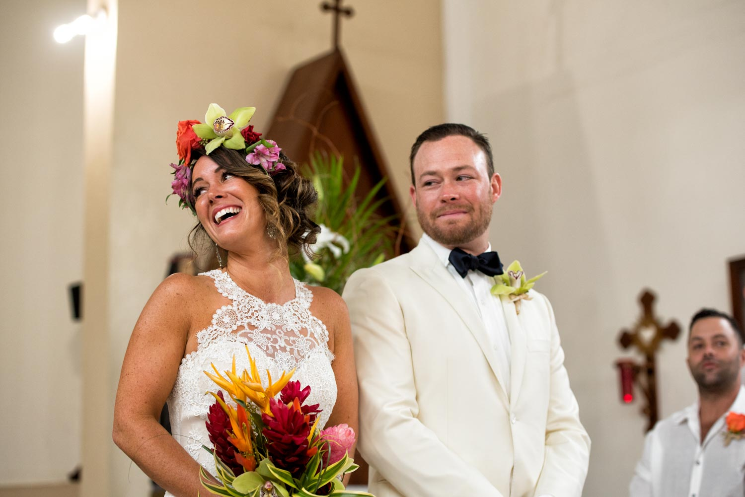 Bride smiling standing next to her fiance holding a bouquet of tropical flowers inside the church.