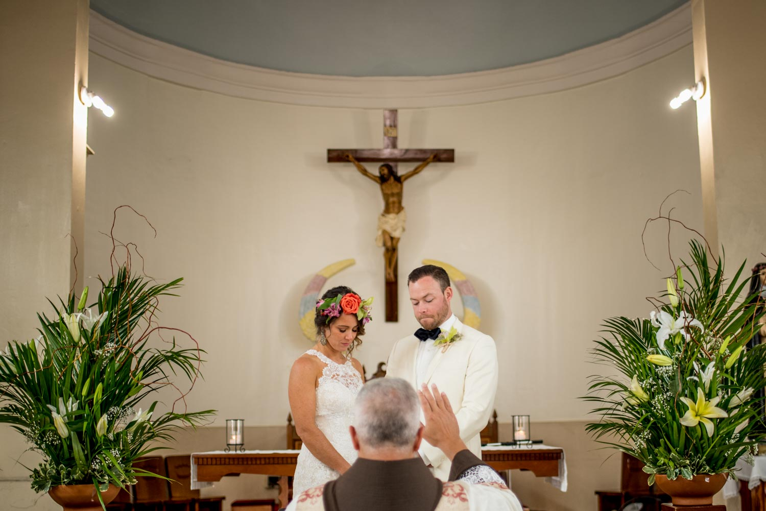 The father blessing the happy couple in front of a catholic cross.