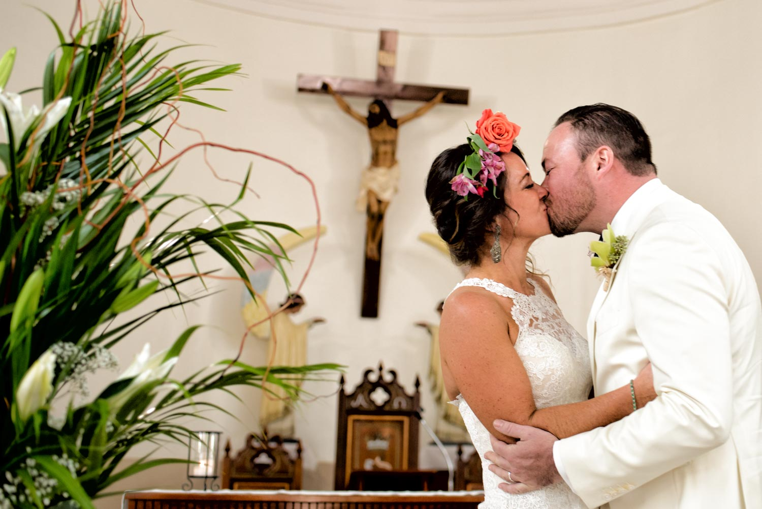 The bride and grooms first kiss in from of a catholic cross inside the church.
