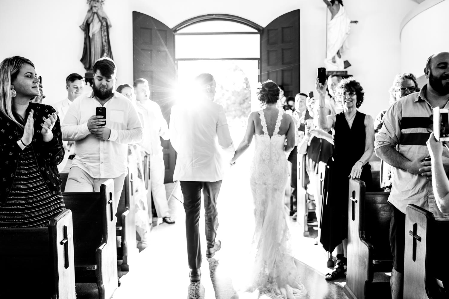 Black and white photograph of the bride and groom from behind exiting the church into the bright sunlight.