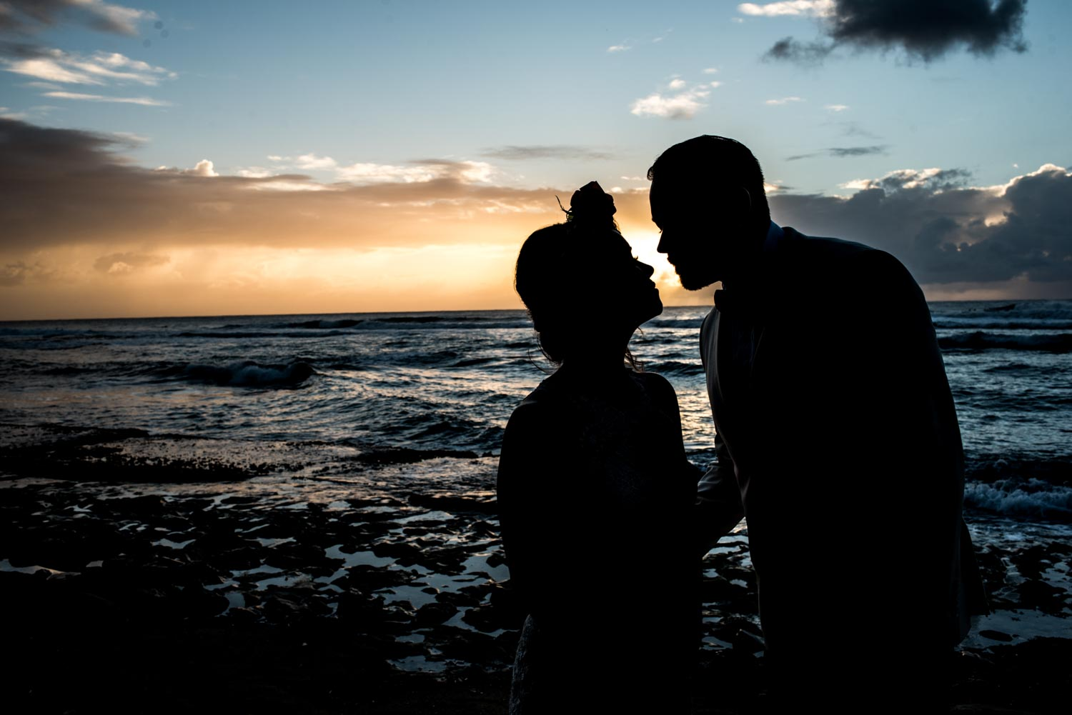 Silhouette of the bride and groom looking at eachother on the beach during a yellow sunset.