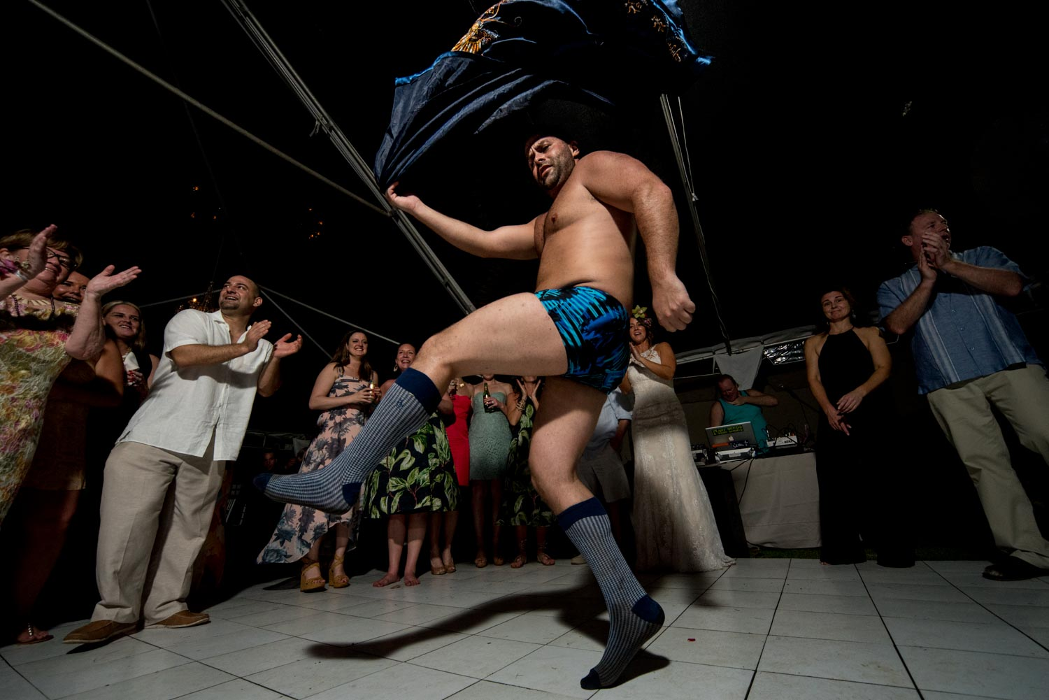 The best man dancing in his underwear spinning a robe surrounded by cheering guests during the wedding reception.