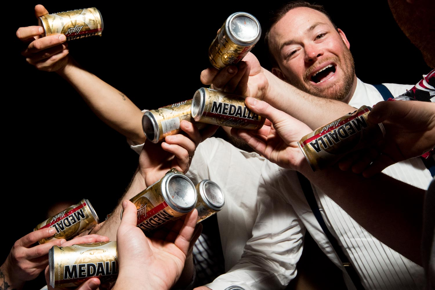 Groom wearing white shirt surrounded by Medalla beer cans that his friends are about to chug.
