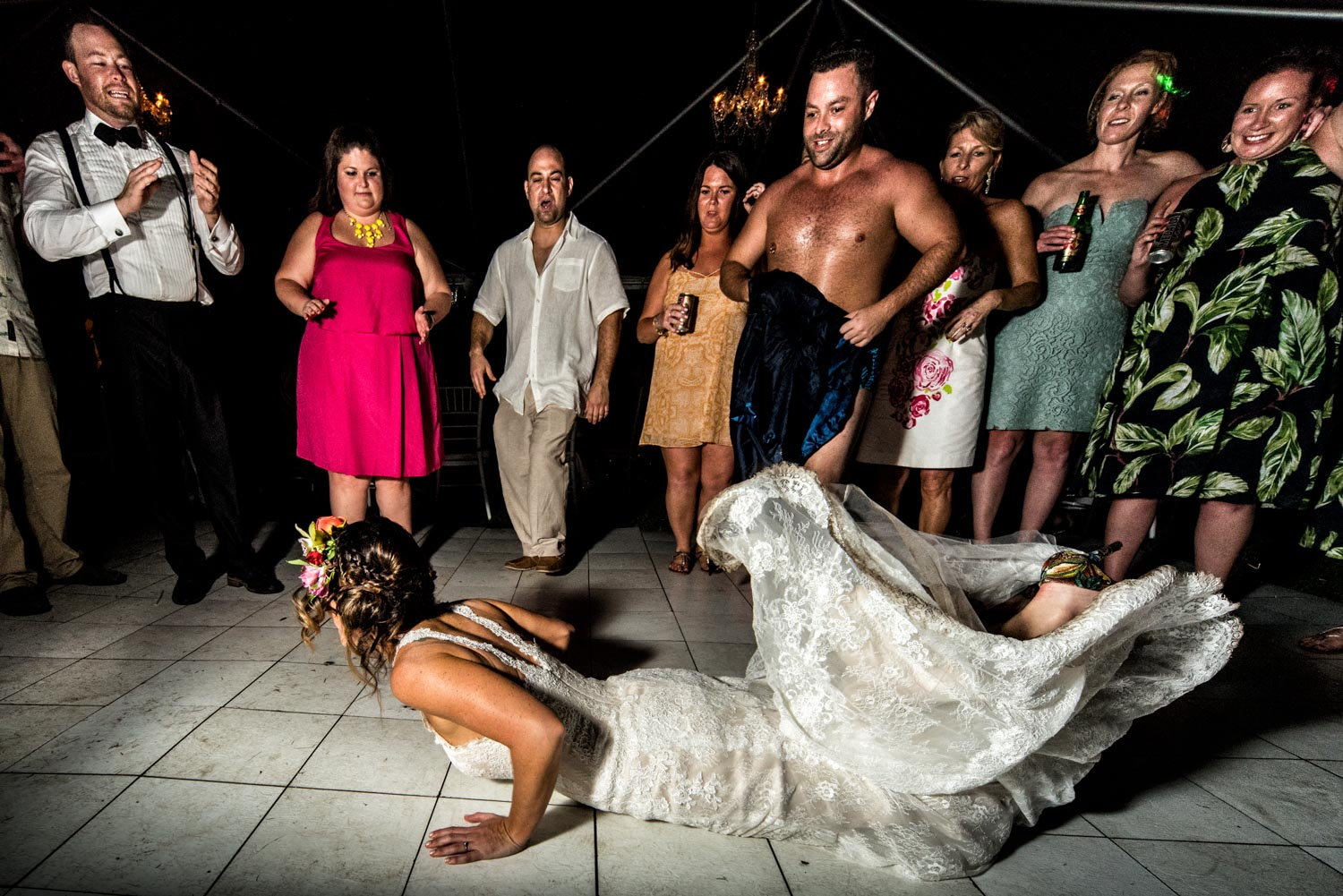 Bride wearing white wedding dress doing a break dance move on the dirty dance floor.