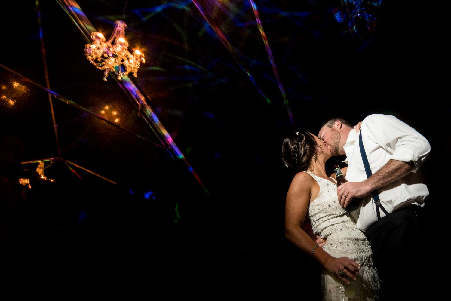 Bride and groom kissing in the dark reception area under a crystal chandelier.