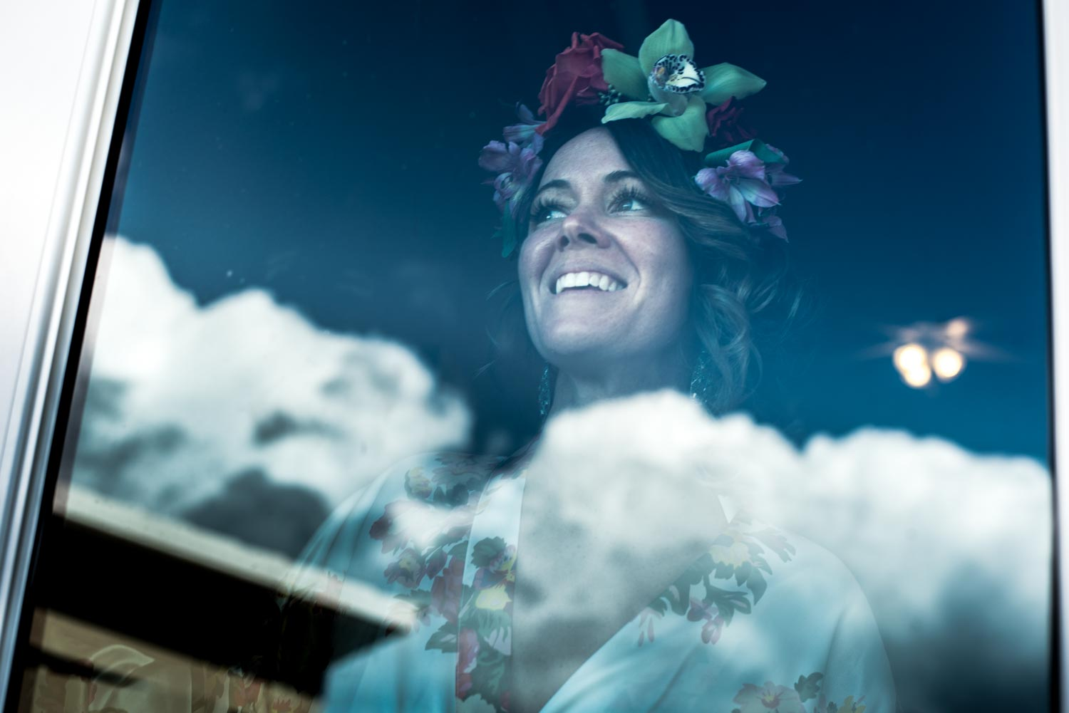Bride wearing a tropical flower crown looks out of a window the blue sky and clouds are reflected in the glass.
