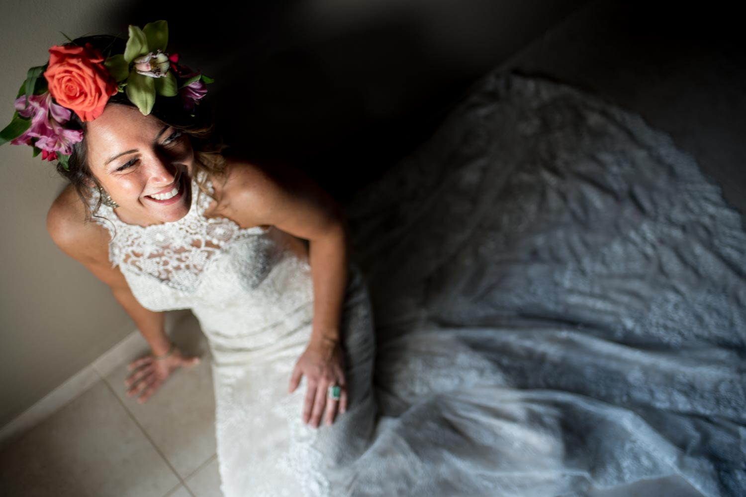 Bride sitting on the ground wearing a white wedding dress and tropical flower crown