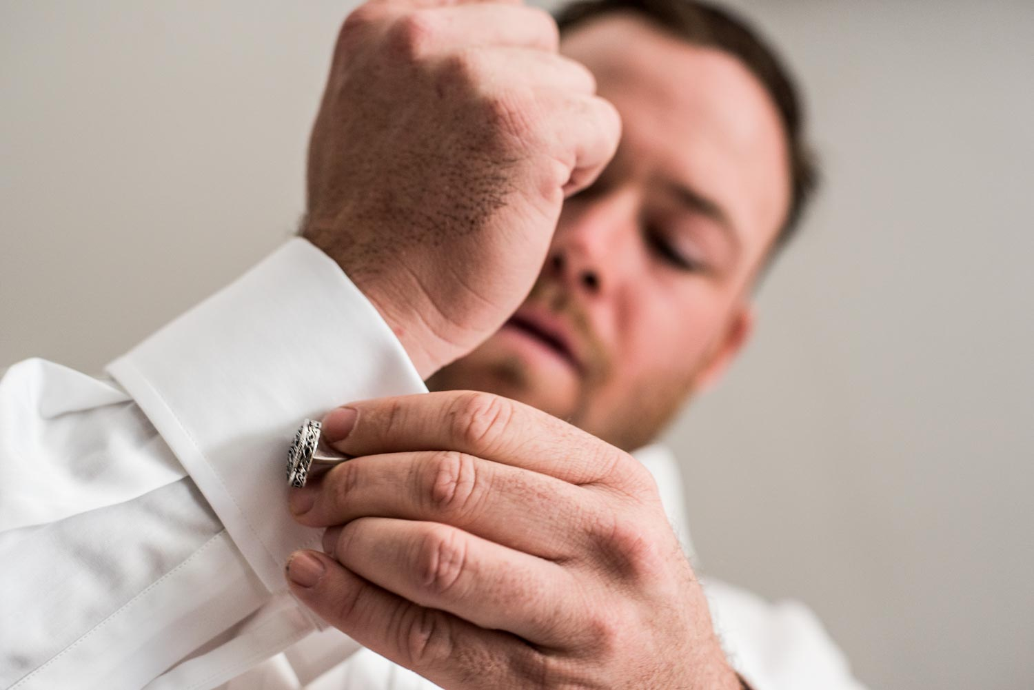 Low angle photograph of a groom putting silver cuff links into his white shirt.