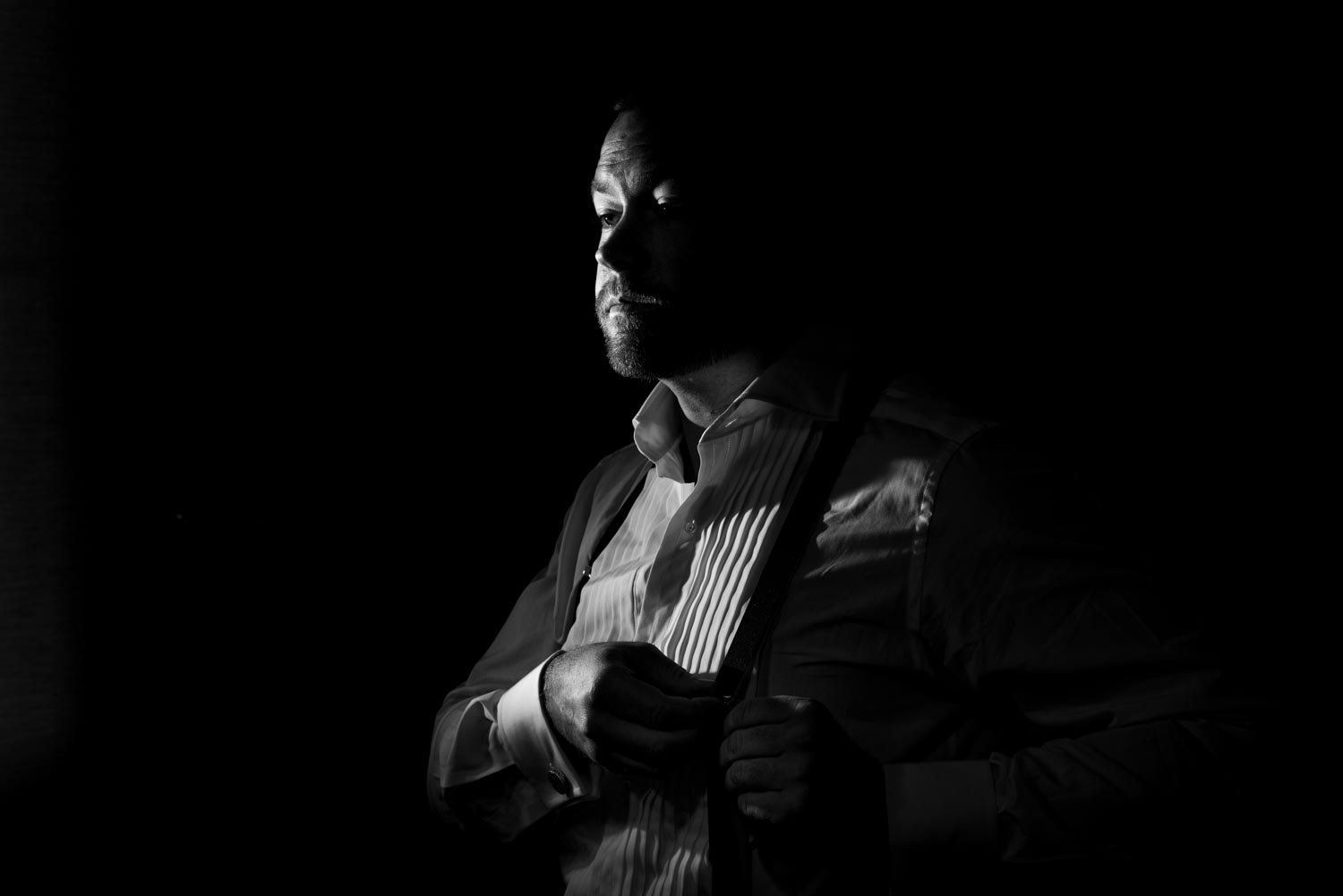 Dramatic black and white portrait of the groom taken inside his room before the wedding.
