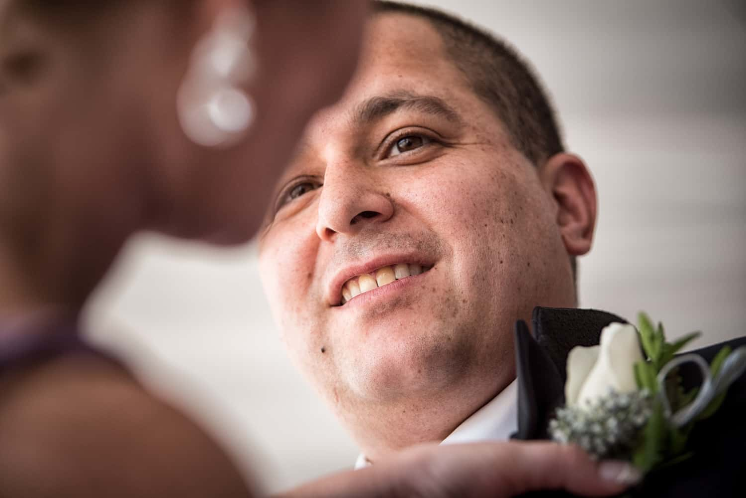 Grooms face smiling while someone pins a white flower to his purple vest.