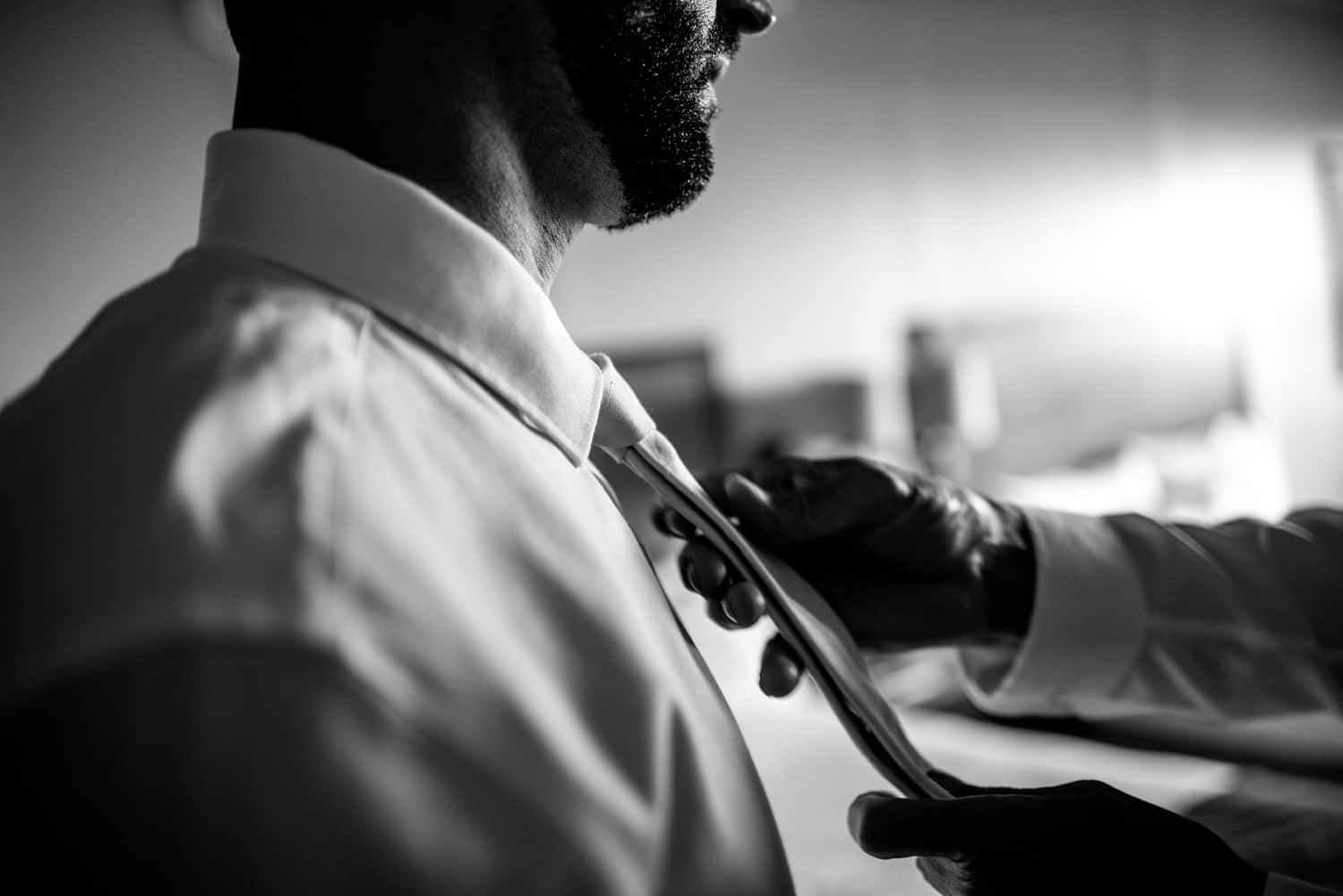 A groomsman's hands carefully tie the grooms tie before the wedding ceremony.