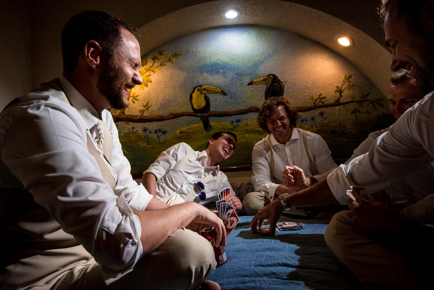 groomsman playing cards on a bed in front of a tropical mural