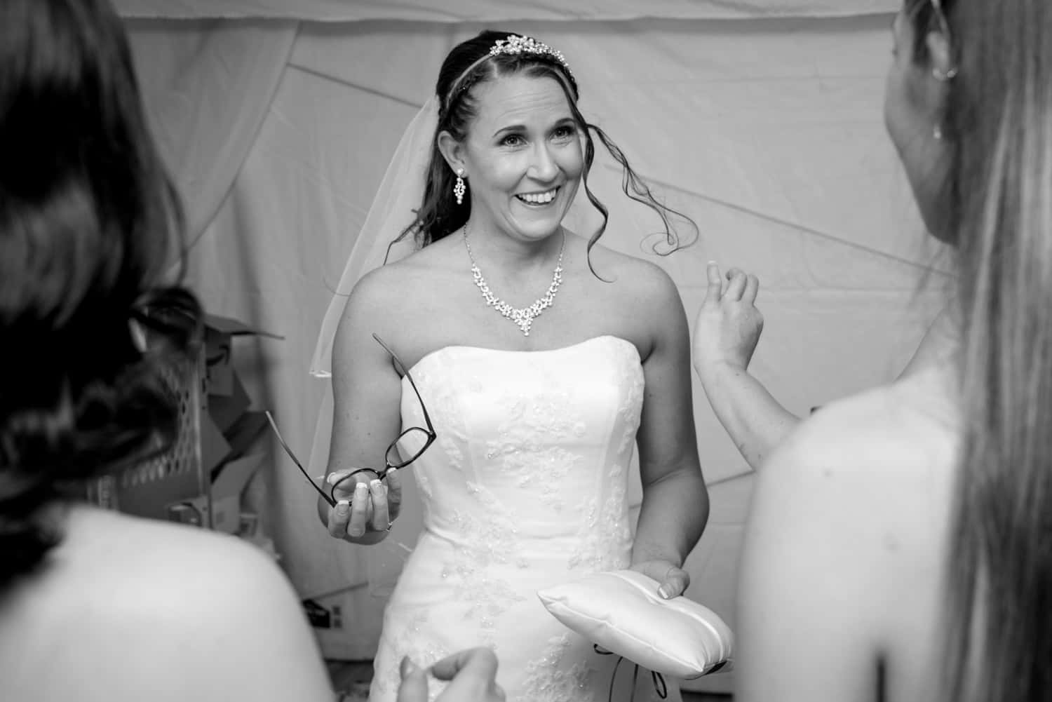 Bride wearing a white wedding dress holds her glasses in her left hand and a pillow in the other while looking at her bridesmaids.