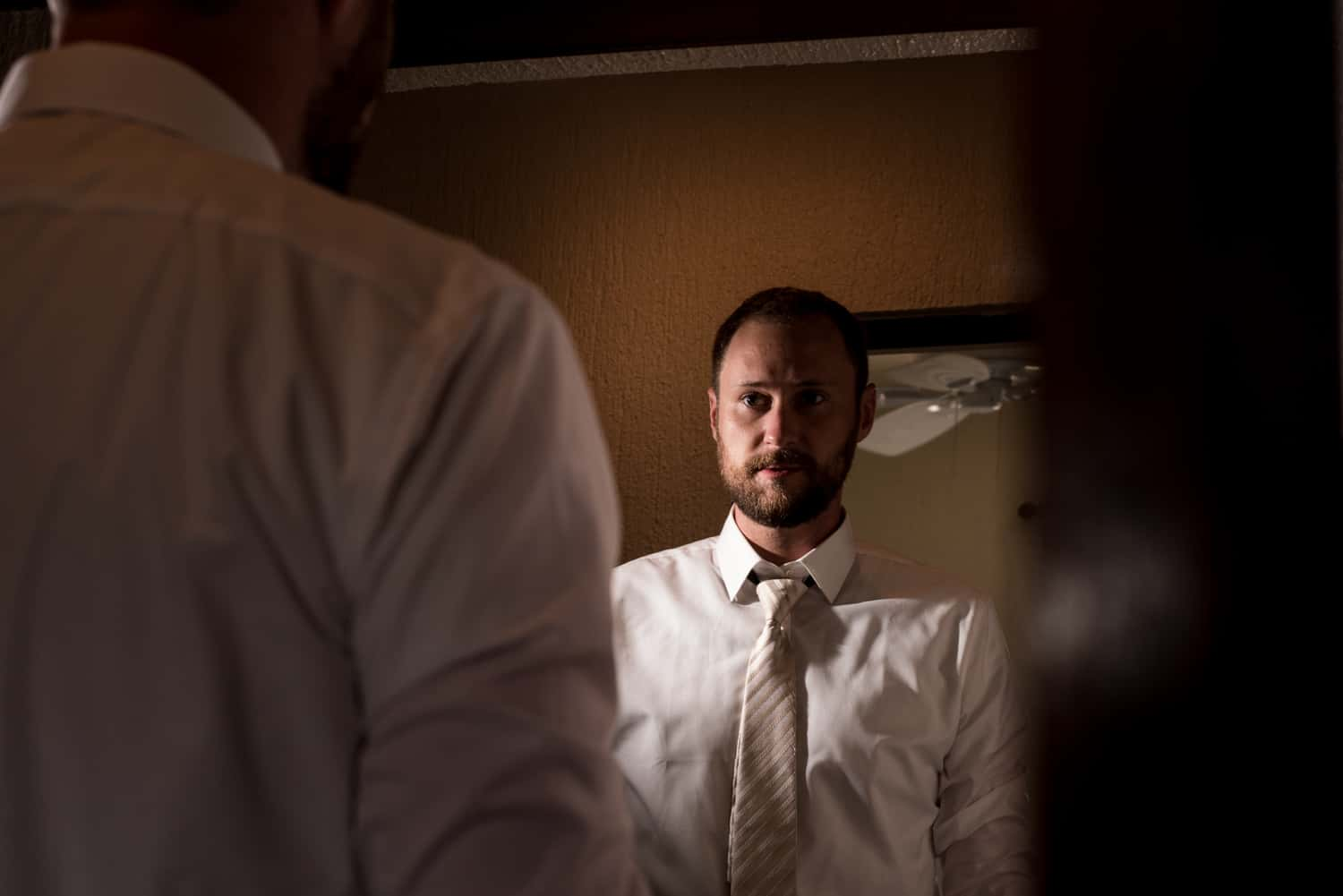 Groom looking at himself in the mirror