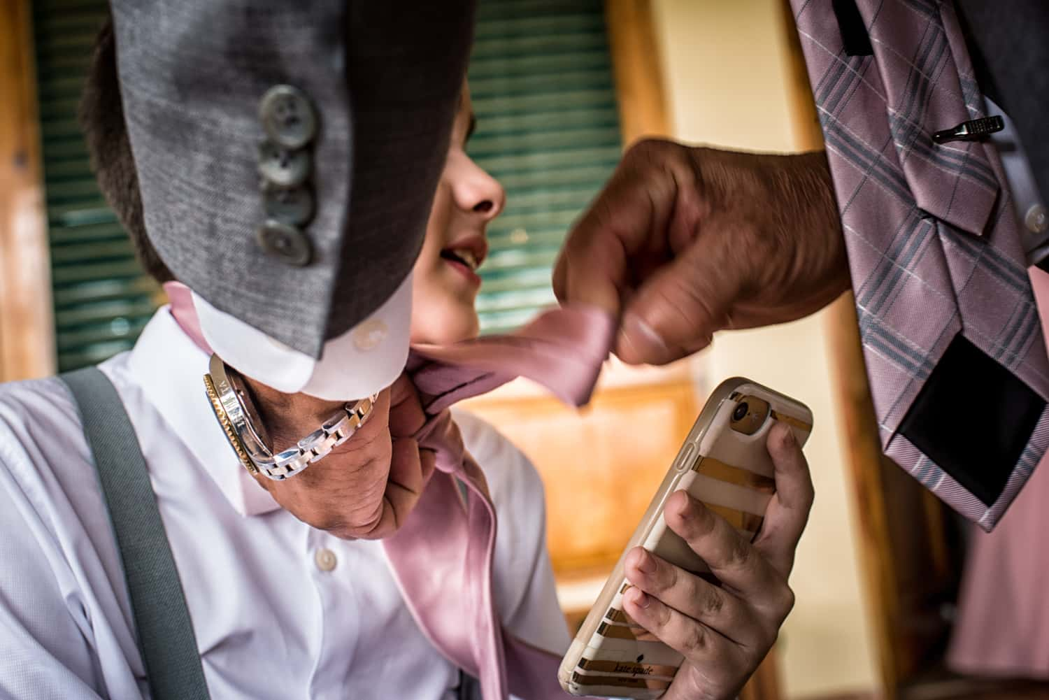 The young boy ring bearer in a white shirt plays on his mothers gold iphone while his grandfathers hands tie his pink tie.