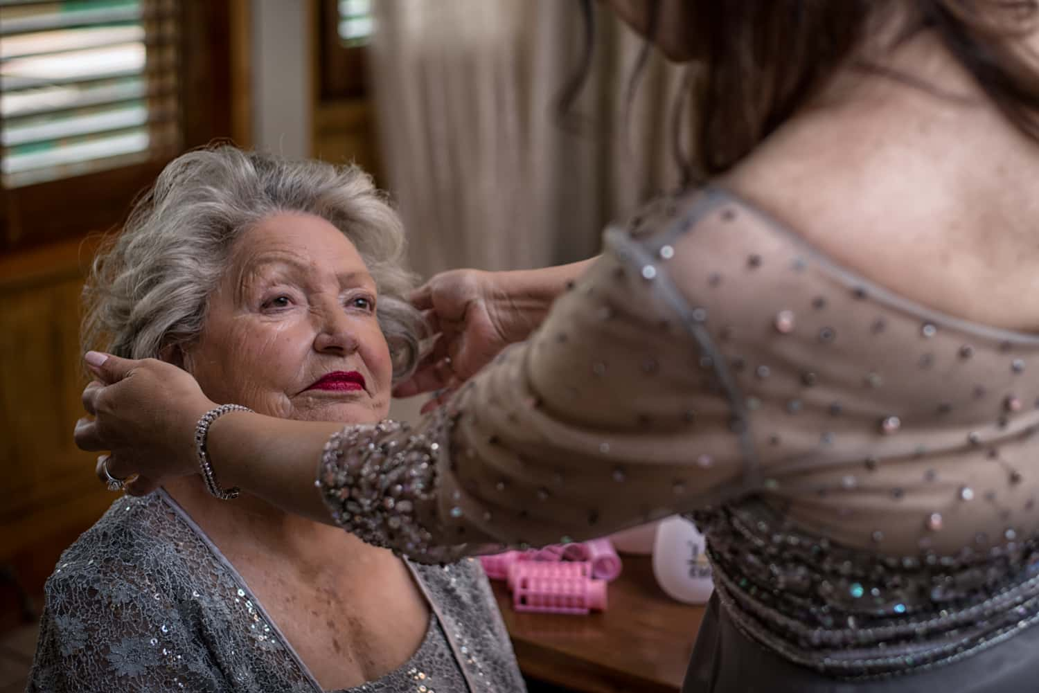 The mother of the bride fixes the hair of the grandmother of the bride