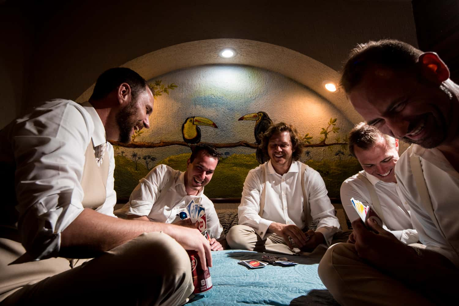Groomsmen laughing playing cards
