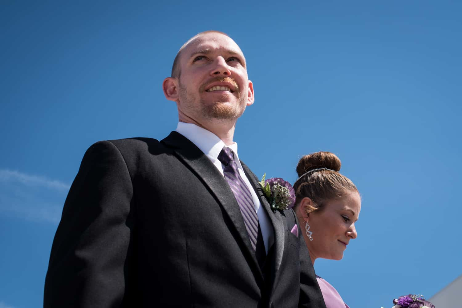 Low angle photograph of groomsman and bridesmaid wearing purple flowers in front of a big blue sky.