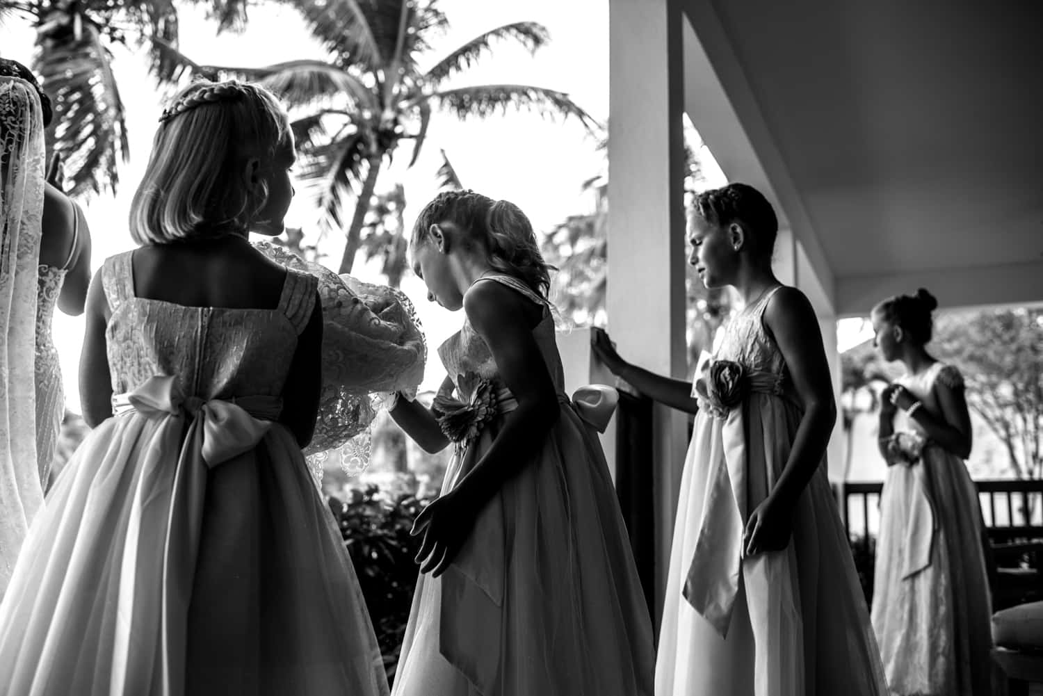 Black and white photograph of four bridesmaids leaning against an outdoor railing.