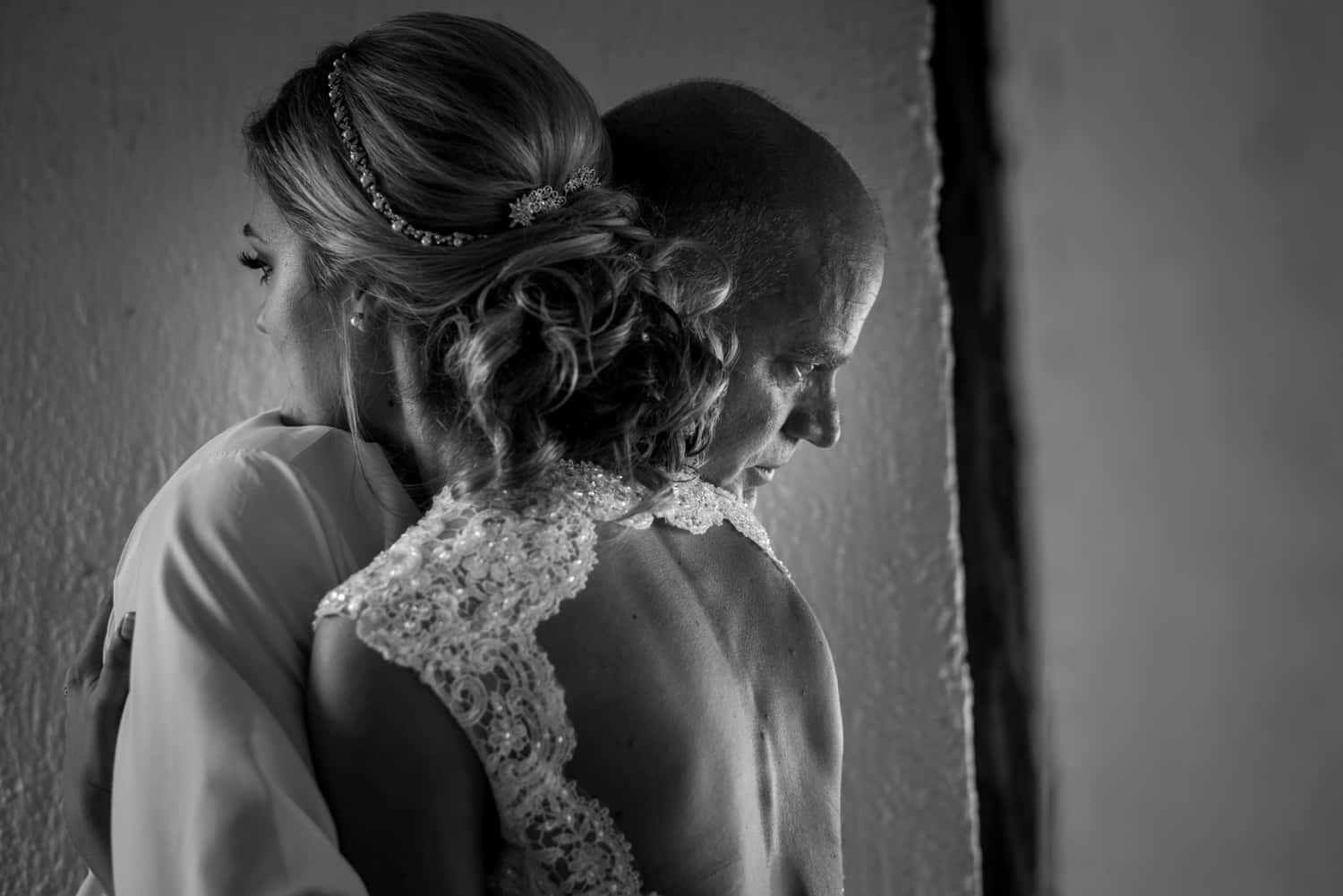 Black and white photograph of bride hugging her father