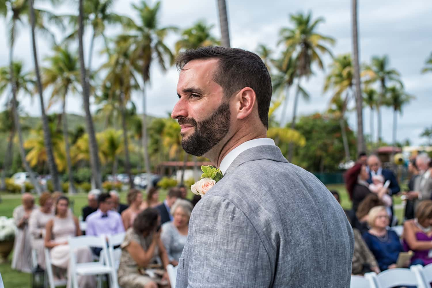 Groom waiting at the alter in front of his guests with palm trees in the distance.