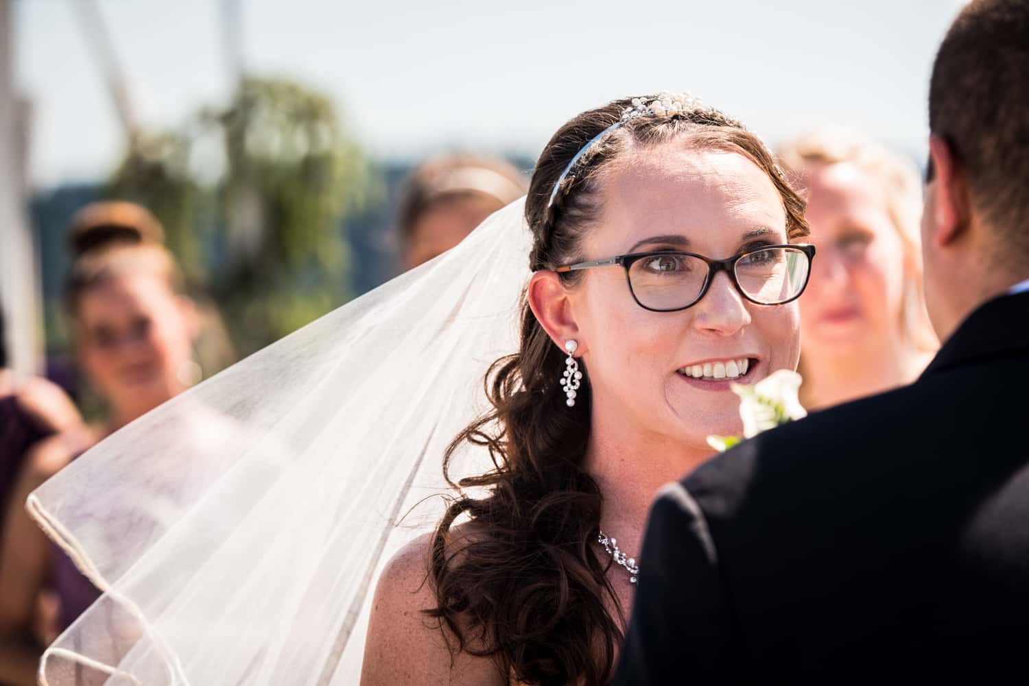 Bride wearing black glasses and a veil looking at her groom during the ceremony.