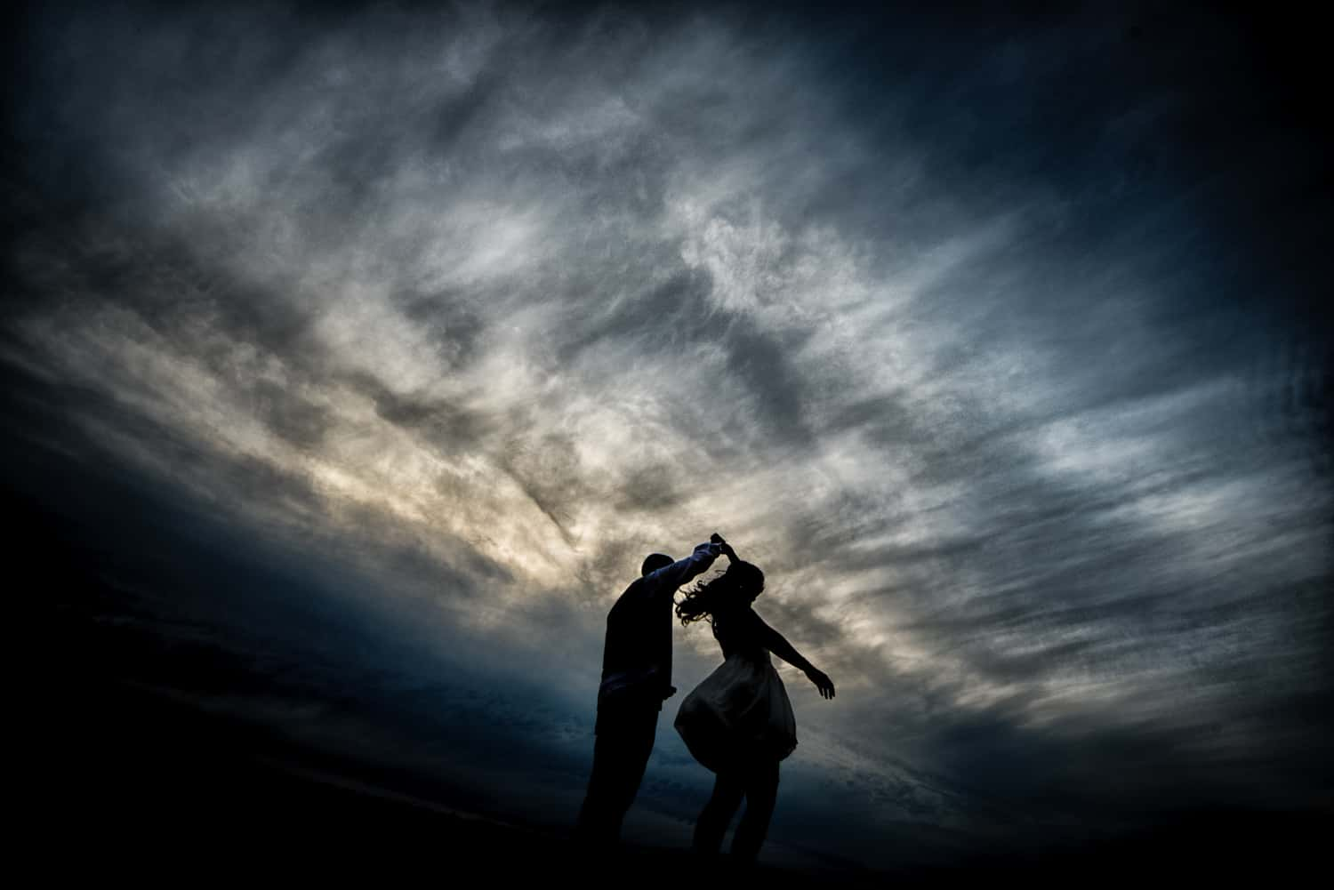 Bride and groom twirling in front of dramatic cloudy sky