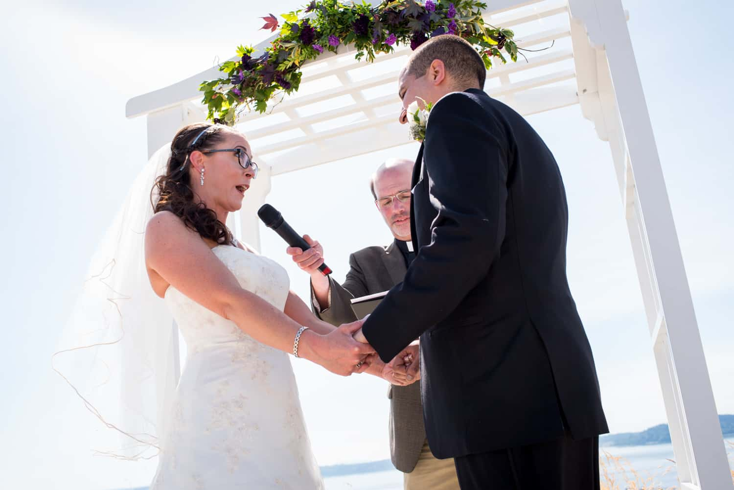 Officiant holds the microphone to the brides face while she recites her vows beneath a white arch with purple flowers.