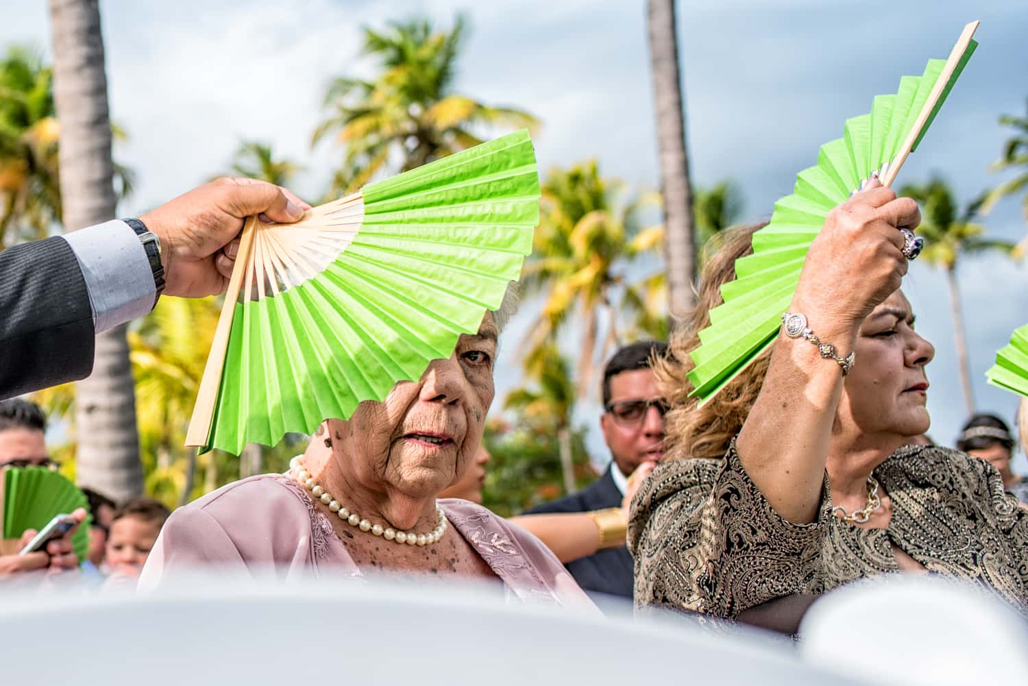 Man fanning an old woman with a green hand fan sitting at the wedding ceremony.