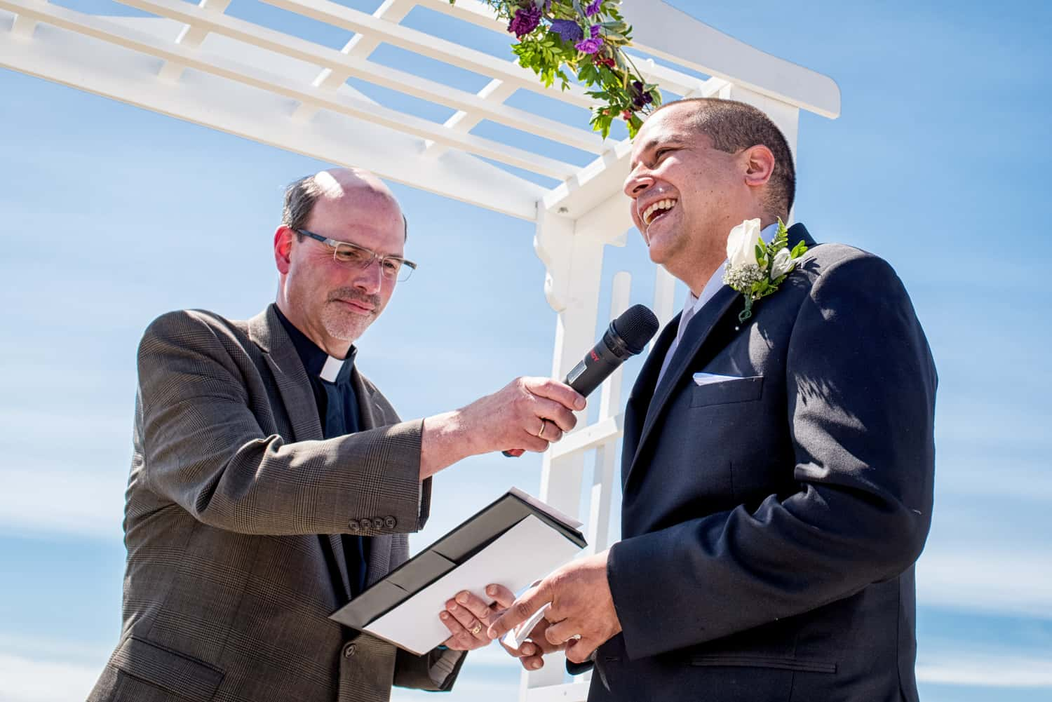 Officiant holds a microphone to the grooms mouth while he reads his vows. Behind them is a blue sky and a white arch with purple flowers.
