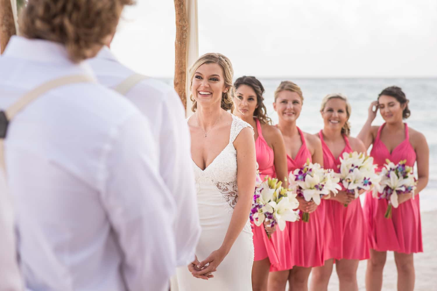 Bride with bridesmaids in pink dresses during beach wedding in Tulum Mexico