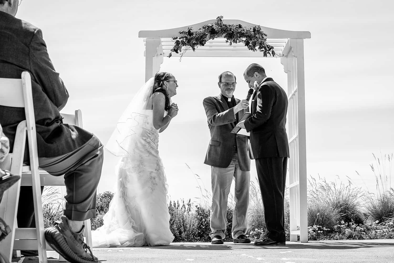 Bride clasping her hands together while the groom reads his vows during their Chambers bay golf club wedding