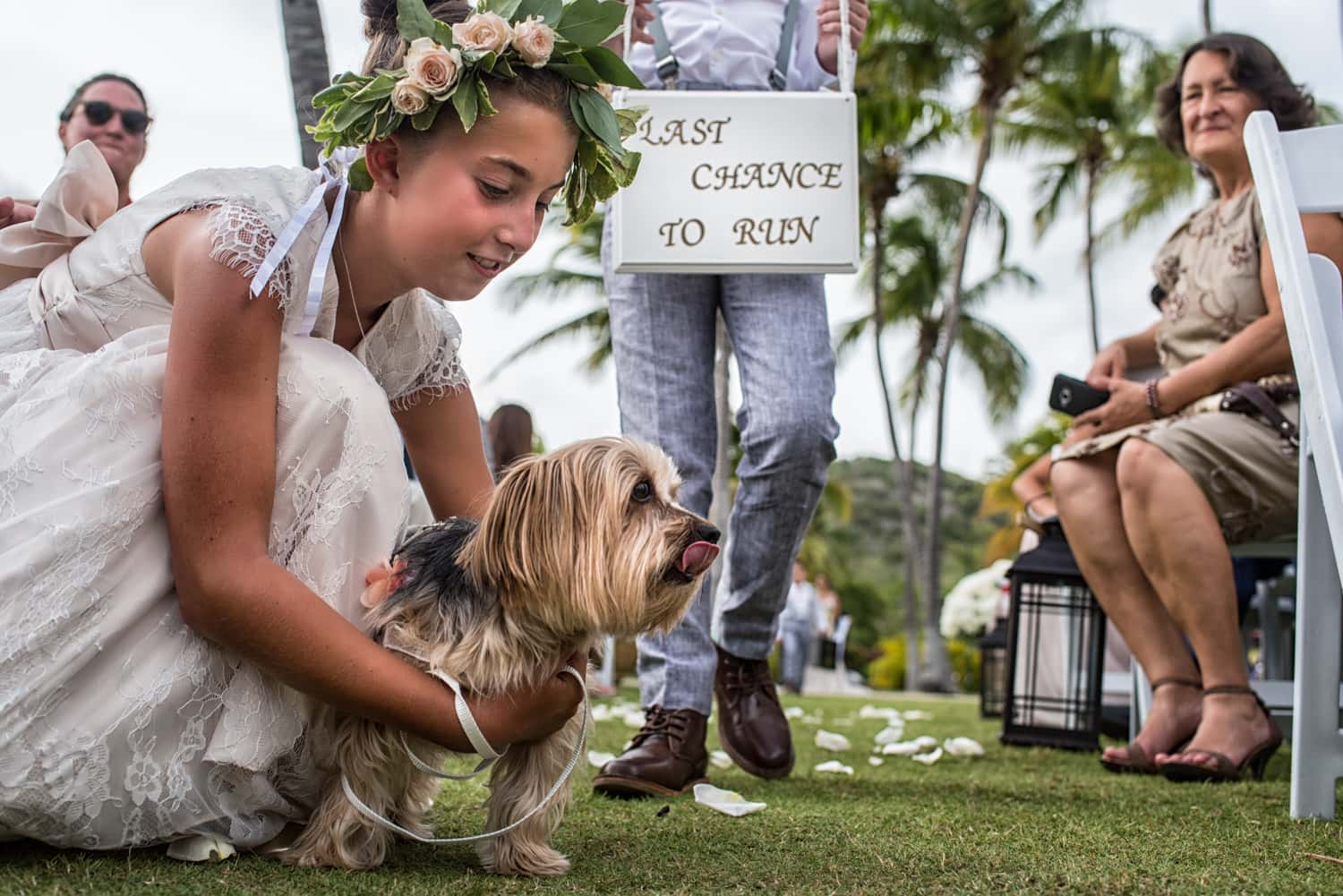 Flower girl holds a dog in the aisle of a wedding ceremony in Puerto Rico.
