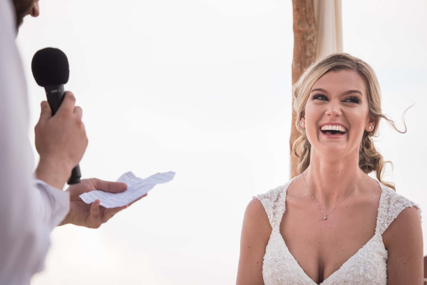 Bride smiling while groom reads vows