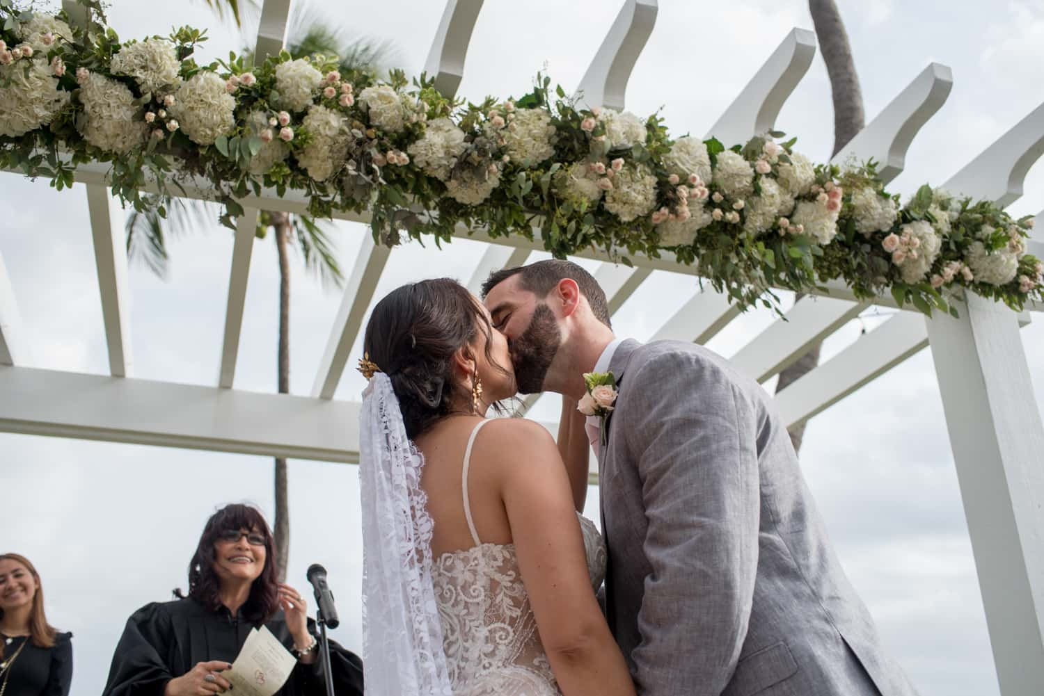 Bride and groom kiss under floral arch