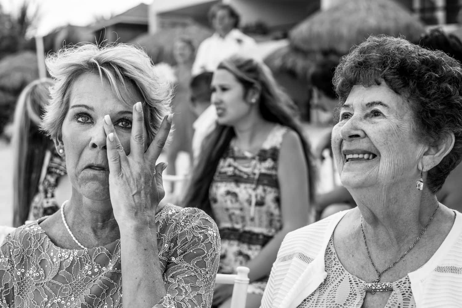 Mother and grandmother crying during wedding ceremony.