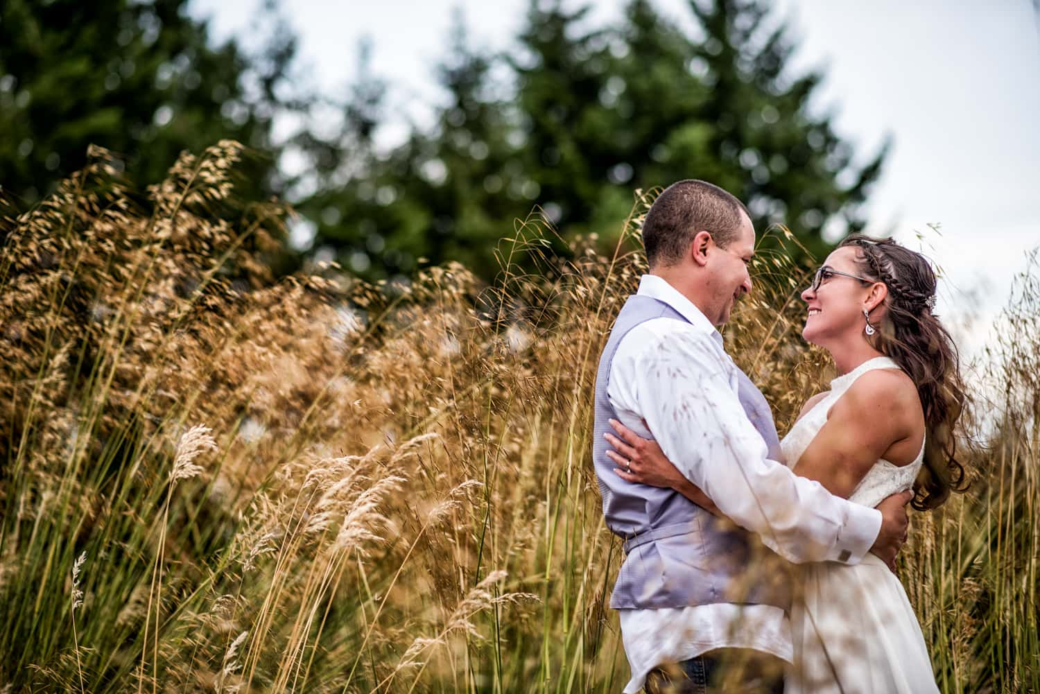 Bride and groom holding each other and looking into each others eyes while standing in a field of tall golden grass.
