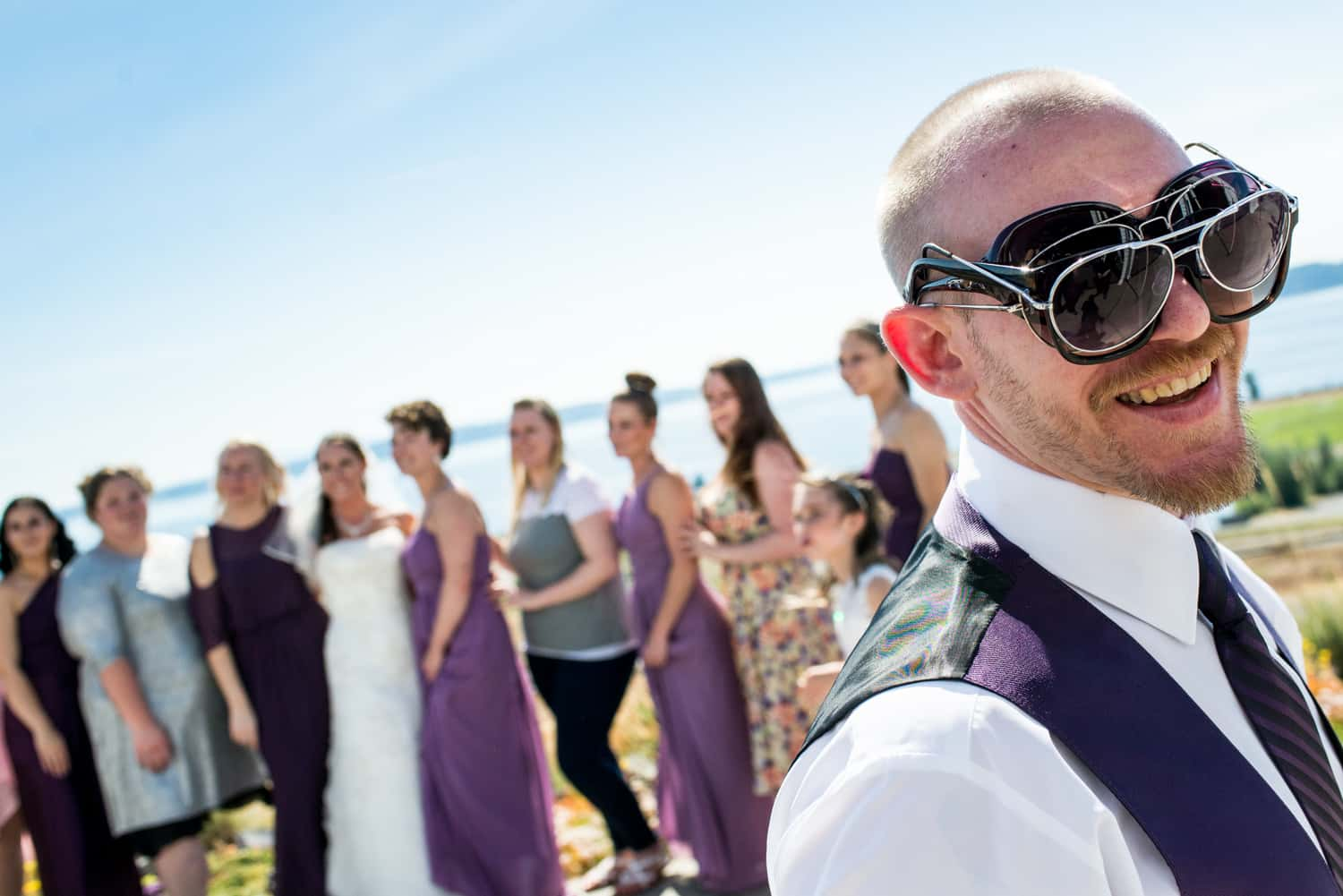 Groomsman goofing off during the family portraits by wearing 6 pairs of sunglasses on his face.