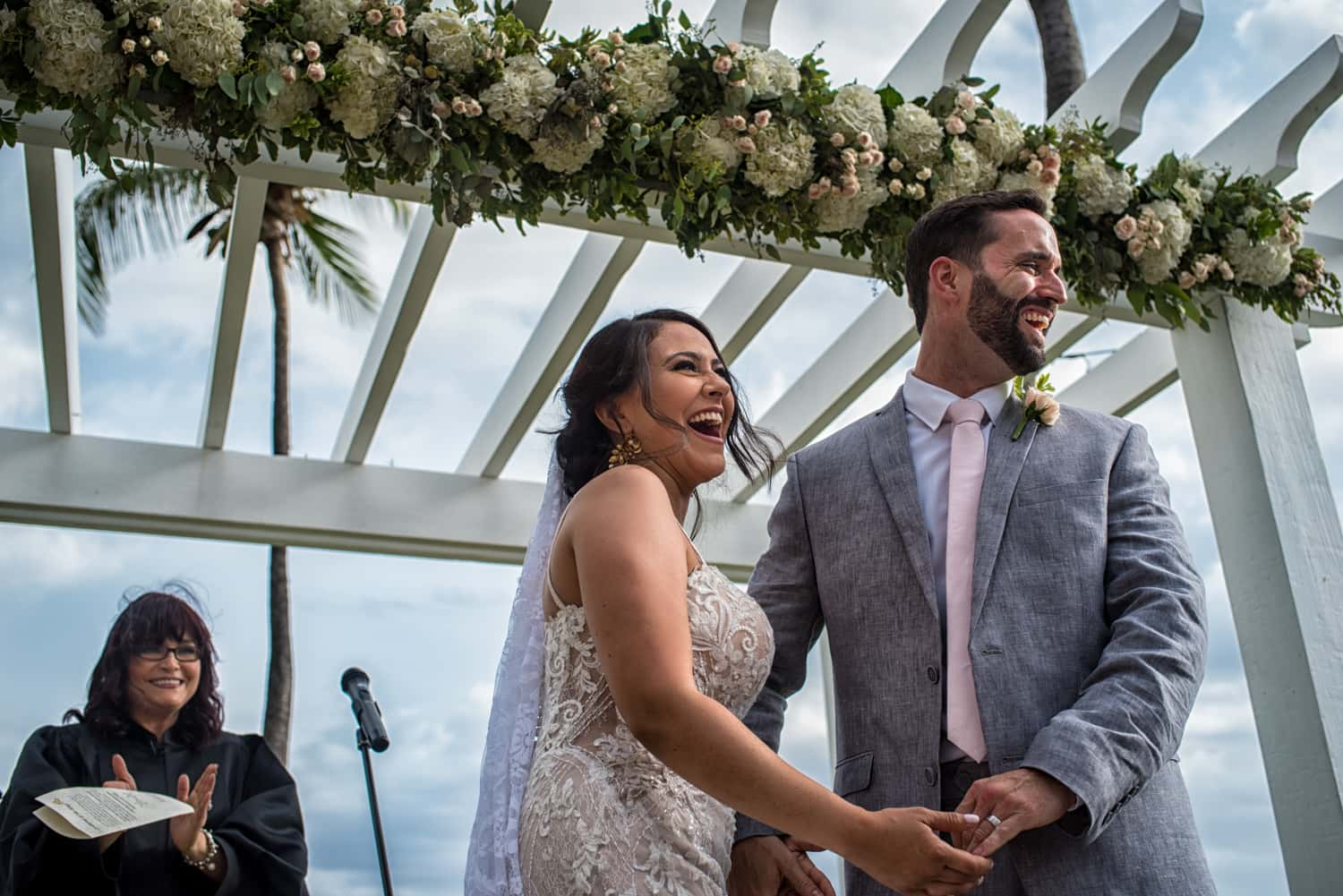 Bride and groom under their floral wedding arch