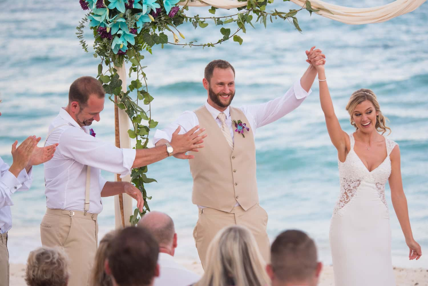 Bride and groom cheering during beach wedding in Tulum Mexico