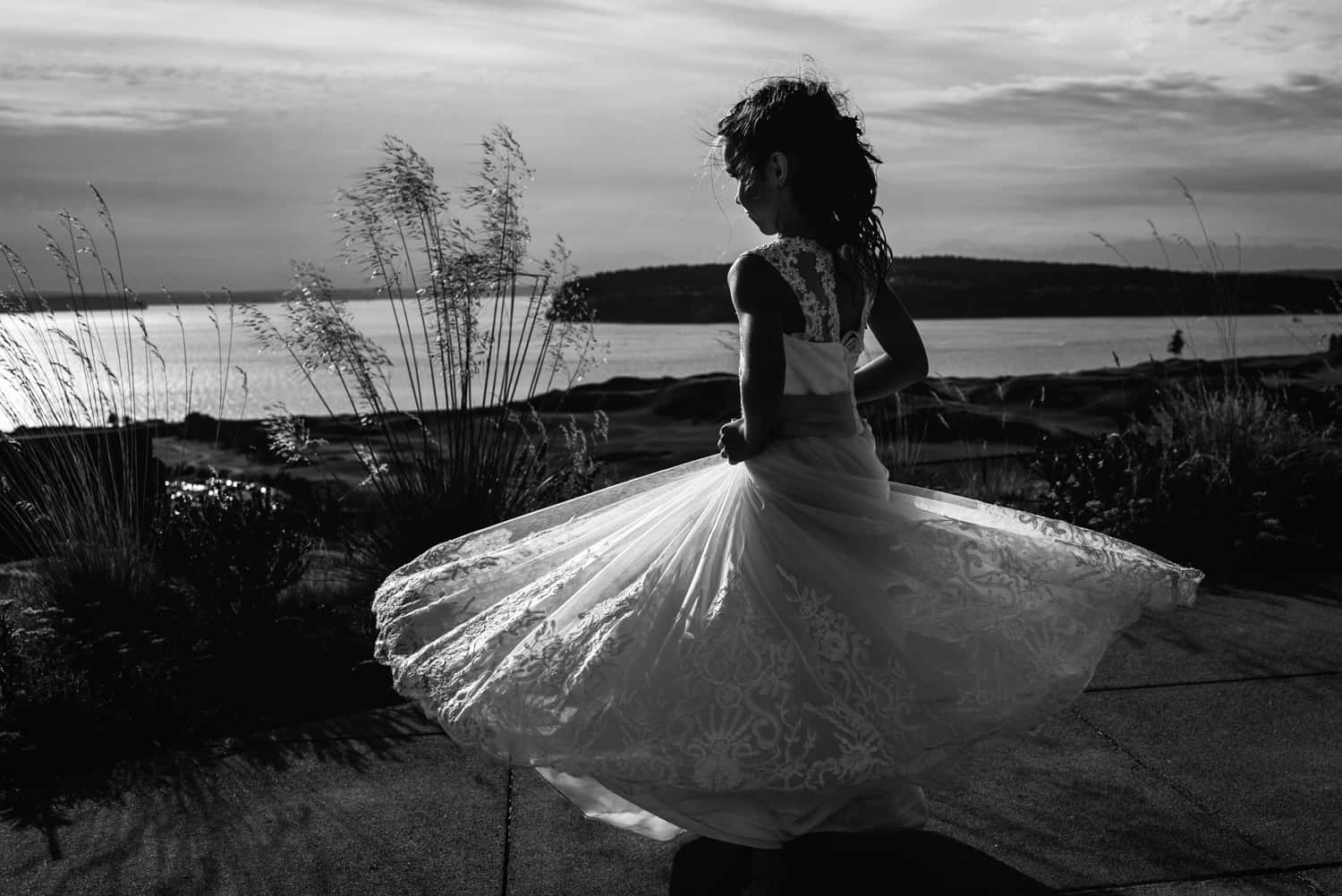 Black and white photograph of a girl twirling in her flower girl dress looking out at the puget sound.