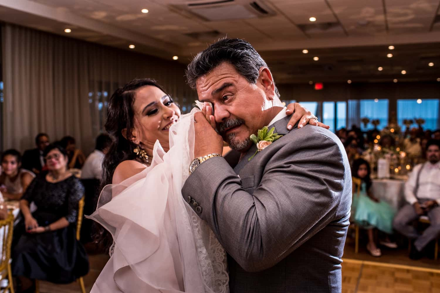 bride wiping tears from her fathers eyes during the wedding reception