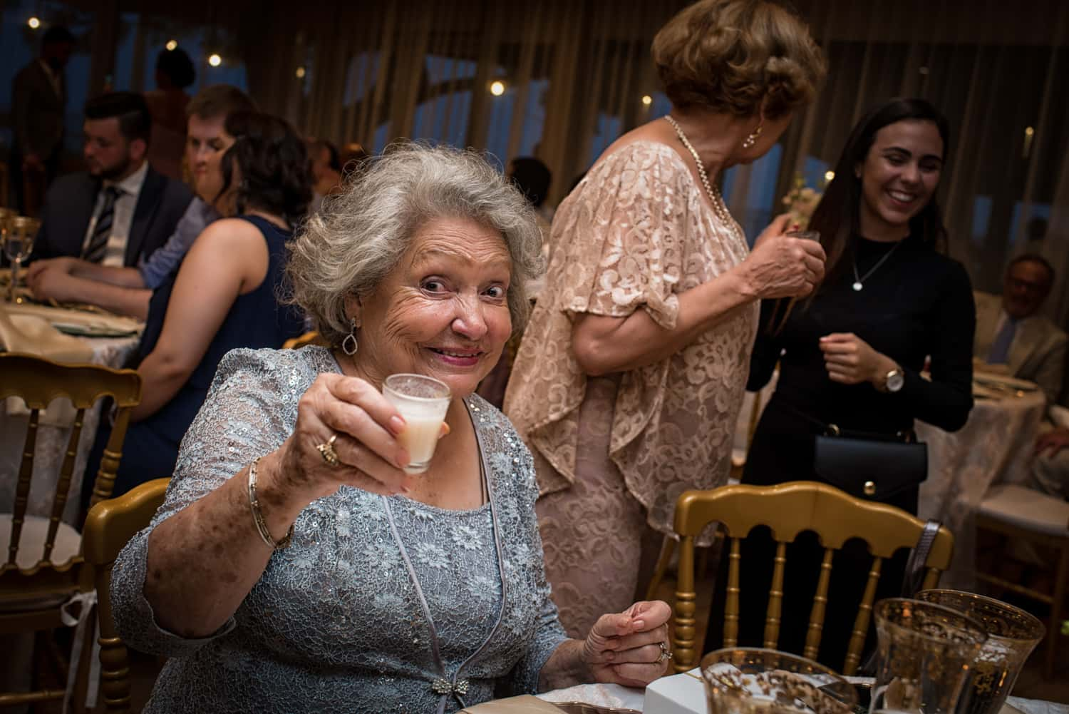 Coquito sipping grandmother at a wedding