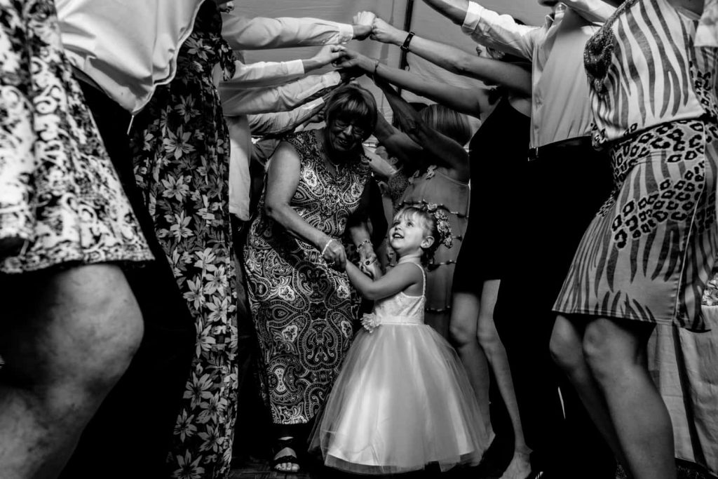 Flower girl under a bunch of arms dancing during a wedding reception.