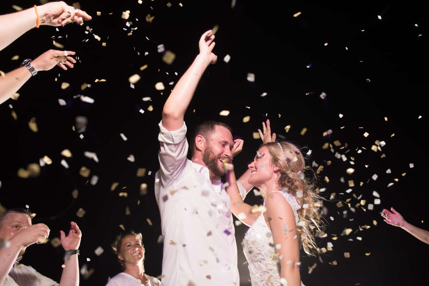 Bride and groom dancing with confetti during wedding reception
